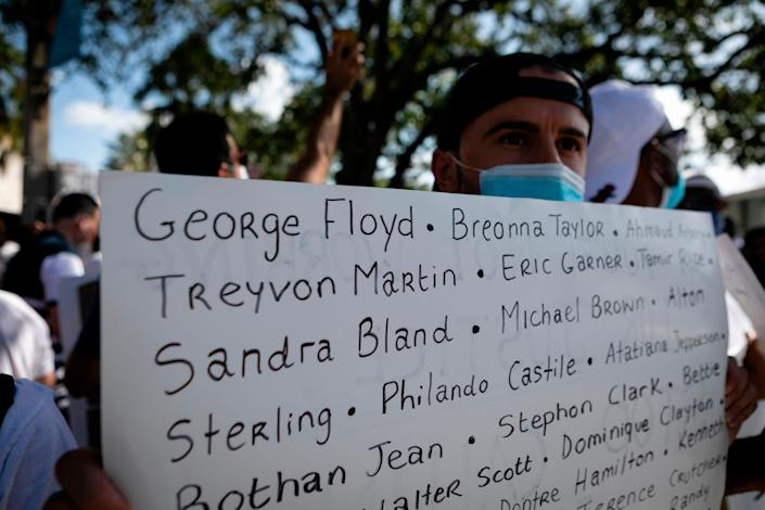 <i>A protester holds a sign with the names of victims of police brutality during a rally in Coral Gables, Florida, on May 30.</i>