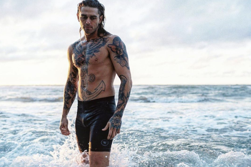 Bachelor In Paradise season three cast member Timm Hanly wearing black shorts while standing in the waves