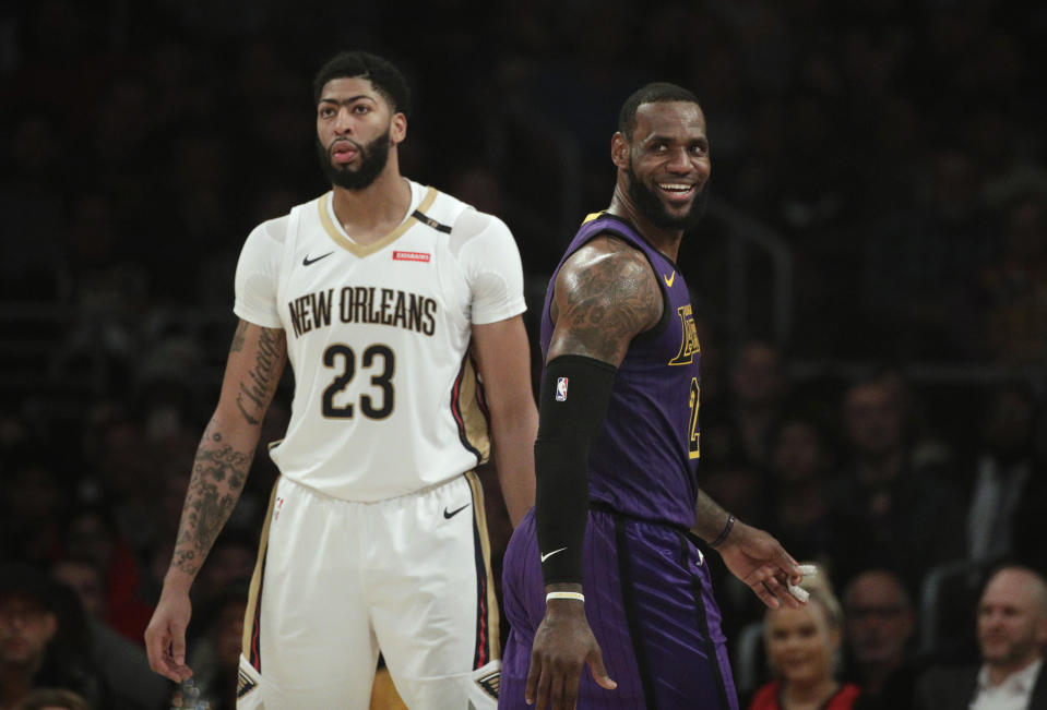 Los Angeles Lakers' LeBron James, right, smiles as he walks past New Orleans Pelicans' Anthony Davis during the first half of an NBA basketball game Friday, Dec. 21, 2018, in Los Angeles. (AP Photo/Jae C. Hong)
