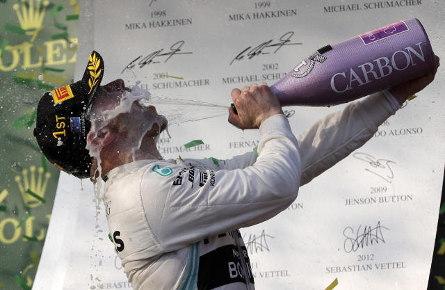 In this Sunday, March 17, 2019, file photo, Mercedes driver Valtteri Bottas of Finland sprays himself with champagne after winning the Australian Formula 1 Grand Prix in Melbourne, Australia. Bottas won ahead of teammate Lewis Hamilton of Britain while Red Bull driver Max Verstappen of the Netherlands placed third. (AP Photo/Rick Rycroft, File)