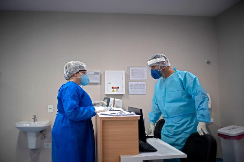 Nurse Hans Bossan (R) speaks with a physician about a patient infected with COVID-19 at the Intensive Care Unit (ICU) of the Doctor Ernesto Che Guevara Public Hospital, in Marica, Rio de Janeiro state, Brazil, on June 6, 2020. - Marathon-like shifts, low salaries and psychological pressure for fear of taking the coronavirus home: this is the routine of nurses in Brazil, where over 181 professionals have died in the front line fighting against the pandemic. (Photo by Mauro Pimentel / AFP) (Photo by MAURO PIMENTEL/AFP via Getty Images)
