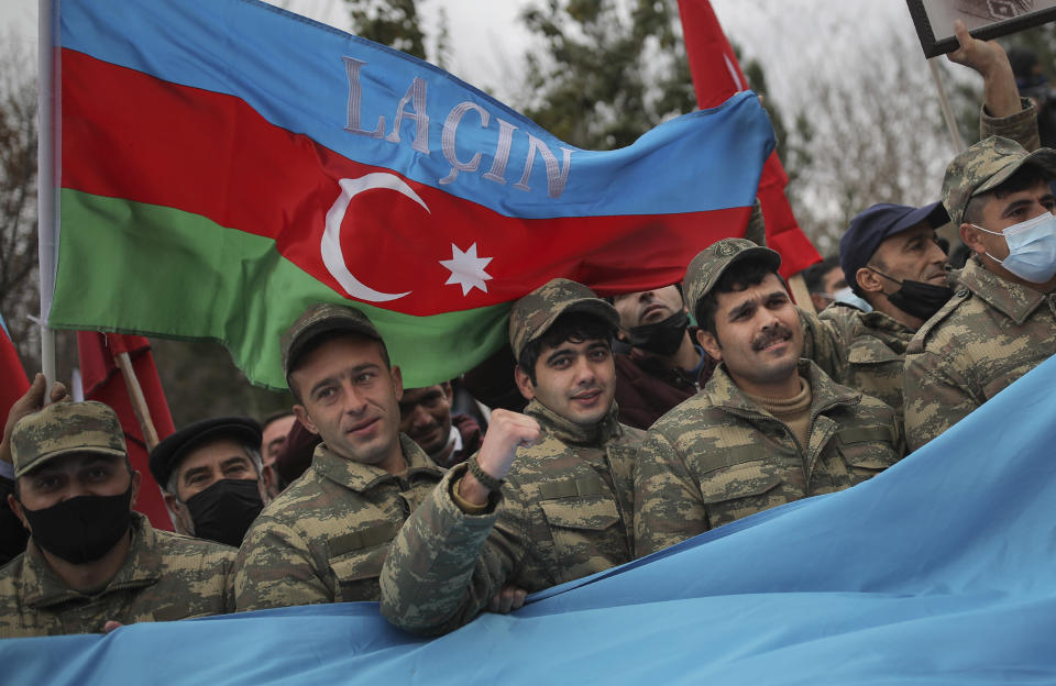 "Azerbaijani soldiers with a national flag with the words ""Lachin"" celebrate the transfer of the Lachin region to Azerbaijan's control, as part of a peace deal that required Armenian forces to cede the Azerbaijani territories they held outside Nagorno-Karabakh, in Aghjabadi, Azerbaijan, Tuesday, Dec. 1, 2020. Azerbaijan has completed the return of territory ceded by Armenia under a Russia-brokered peace deal that ended six weeks of fierce fighting over Nagorno-Karabakh. Azerbaijani President Ilham Aliyev hailed the restoration of control over the Lachin region and other territories as a historic achievement. (AP Photo/Emrah Gurel)"