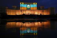 A Euro 2020 themed video mapping is projected on the facade of the communist era built Palace of Parliament, formerly known as the House of the People, in Bucharest, Romania, Friday, June 11, 2021, two days before the city hosts its first game between Austria and North Macedonia. (AP Photo/Vadim Ghirda)