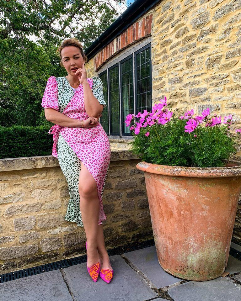 Vera Sahatçiu Ora wears a pink and green leopard print dress in the Cotswolds in June 2020