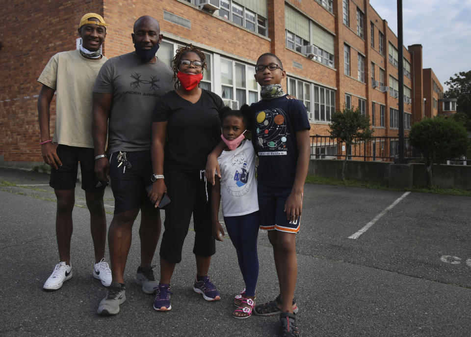 """The Burgess family, from left, Jonathan Jr., 15, Jonathan Sr., Shante, Ava, 6, and Evan, 10, stand outside St. Francis Xavier in Newark, New Jersey, on Thursday, Aug. 6, 2020, as they meet with other parents to discuss the school's closure. """"Closing an inner-city school during a pandemic is not the most godly thing to do,"""" Shante Burgess said. (AP Photo/Jessie Wardarski)"""