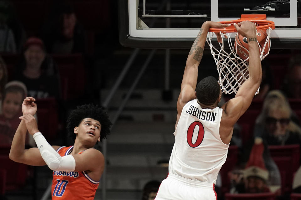 San Diego State forward Keshad Johnson (0) dunks the ball while Boise State guard RayJ Dennis (10) looks on during the second half of an NCAA college basketball game Saturday, Feb 27, 2021, in San Diego. (AP Photo/Gregory Bull)