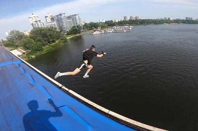 This heart-stopping footage shows a daredevil jumping from a speeding train into a river below