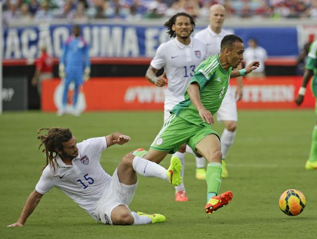 Nigeria's Peter Odemwingie, center, gets control of the ball away from United States's Kyle Beckerman, left, during the first half of an international friendly soccer match in Jacksonville, Fla., Saturday, June 7, 2014. (AP Photo/John Raoux)