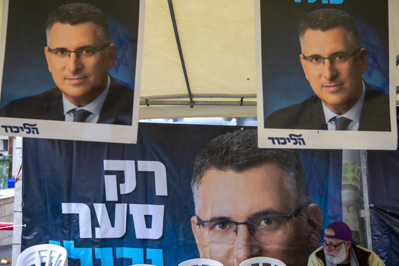 A Likud party member sits by a poster of veteran politician Gideon Saar from the governing Likud Party at a voting center in the northern Israeli city of Hadera, Thursday, Dec. 26, 2019. Israel's governing Likud party was holding primaries on Thursday, in the first serious internal challenge to Israeli Prime Minister Benjamin Netanyahu in his more than a decade in power. Saar hopes to unseat Netanyahu, arguing that he will be better placed to form a government in national elections in March after Netanyahu failed to do so in two repeat elections this year. (AP Photo/Ariel Schalit)