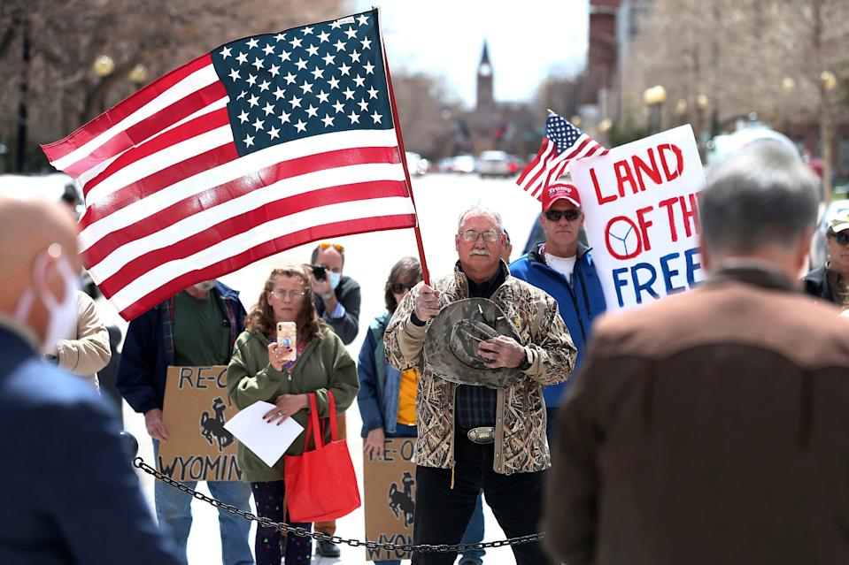 Protesters pray with Wyoming Gov. Mark Gordon during a rally criticizing the state's response to COVID-19 on April 20 outside the state Capitol in Cheyenne.