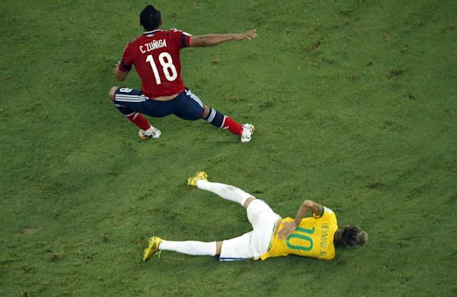Brazil's Neymar holds his back after a hefty challenge from Colombia's Juan Zuniga during the World Cup quarter-final match at the Castelao Stadium in Fortaleza, on July 4, 2014 (AFP Photo/Fabrizio Bensch)