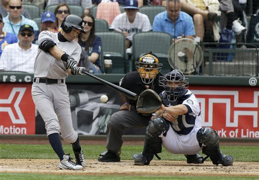 New York Yankees' Ichiro Suzuki, left, makes contact in the second inning of a baseball game as Seattle Mariners catcher Brandon Bantz, right, and home plate umpire Laz Diaz watch on Saturday, June 8, 2013, in Seattle. Suzuki grounded out at first on the play. (AP Photo/Ted S. Warren)