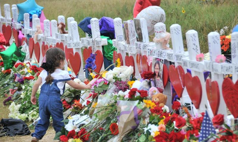 A girl lays flowers at a memorial site for victims killed in a mass shooting in Sutherland Springs, Texas on 12 November 2017.