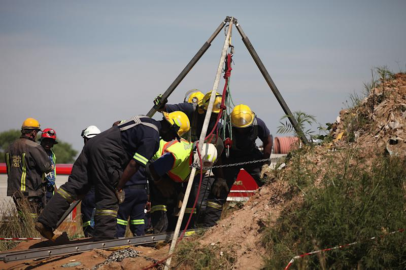 Emergency rescue workers attempt to free trapped illegal miners at a disused gold mine shaft near, Benoni, South Africa, Sunday, Feb. 16, 2014. The South African Press Association reported Sunday that rescue teams were able to speak to about 30 miners near the top of an old gold mine shaft whose entrance was covered by a large rock. Those miners said as many as 200 others were trapped further down a steep tunnel at the mine in Benoni, on the outskirts of Johannesburg (AP Photo)