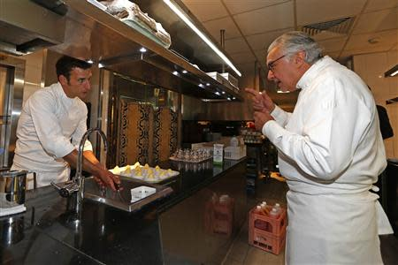 French chef Alain Ducasse speaks with his head chef Christophe Saintagne (L) in the kitchen of the Le Meurice Restaurant in Paris September 4, 2013. REUTERS/Charles Platiau