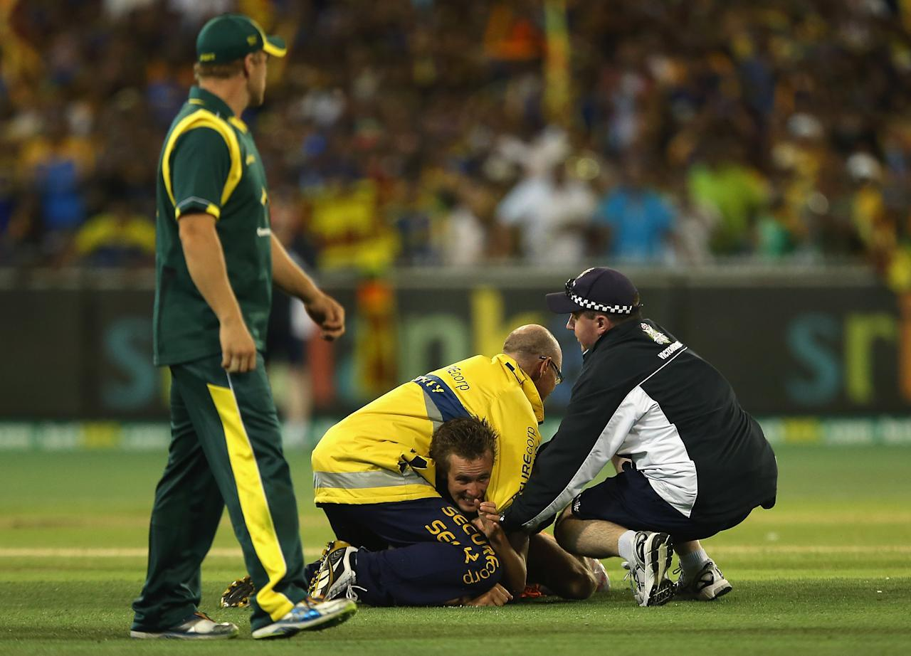 MELBOURNE, AUSTRALIA - JANUARY 11:  A pitch invader is grabbed by security during game one of the Commonwealth Bank One Day International series between Australia and Sri Lanka at Melbourne Cricket Ground on January 11, 2013 in Melbourne, Australia.  (Photo by Quinn Rooney/Getty Images)
