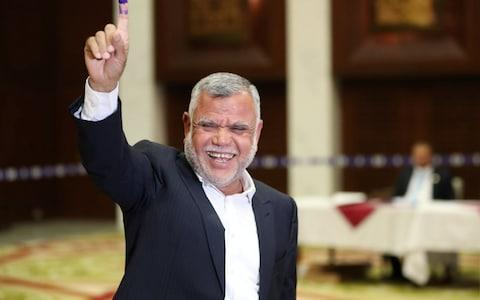 <span>Hadi al-Amiri, a Shia militia commander running for prime minister, shows his ink-stained finger after casting his vote at a polling station during the parliamentary election in Baghdad</span> <span>Credit: REUTERS/Ahmed Jadallah </span>
