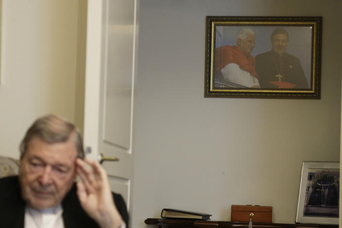 A picture of Pope Benedict XVI and Australian Cardinal George Pell taken in Sydney during the 2008 World Youth Day hangs on a wall of Cardinal Pell's home while he is interviewed by The Associated Press at the Vatican, Thursday, May 20, 2021. Pell, who was convicted and then acquitted of sex abuse charges in his native Australia, is spending his newfound freedom in Rome. (AP Photo/Gregorio Borgia)