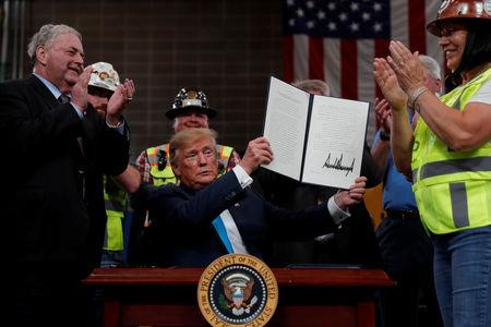 U.S. President Donald Trump displays an executive order he signed on energy and infrastructure at the International Union of Operating Engineers International Training and Education Center in Crosby, Texas, U.S., April 10, 2019. REUTERS/Carlos Barria