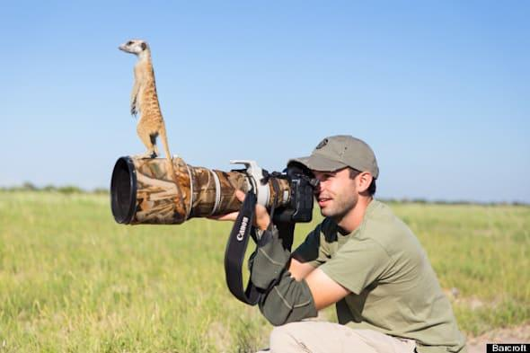 ***EXCLUSIVE***MAKGADIKGADI, BOTSWANA - JANUARY 2014: Will Burrard-Lucas takes a photo while a Meerkat perches on his lens on January 2014 in Makgadikgadi, Botswana.THESE adorable Meerkats used a photographer as a look out post before trying their hand at taking pictures. The beautiful images were caught by wildlife photographer Will Burrard-Lucas after he spent six days with the quirky new families in the Makgadikgadi region of Botswana. Will has photographed Meerkats in the past and was delighted when he realised he would be shooting new arrivals.PHOTOGRAPH BY Will Burrard - Lucas / Barcroft MediaUK Office, London.T +44 845 370 2233W www.barcroftmedia.comUSA Office, New York City.T +1 212 796 2458W www.barcroftusa.comIndian Office, Delhi.T +91 11 4053 2429W www.barcroftindia.com