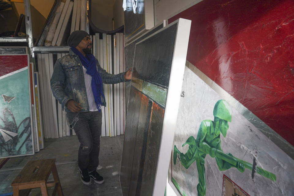 "Painter Guy Stanley Philoche, a 43-year-old Haitian immigrant and star in the New York art world, shows some of his latest works during an interview at his East Harlem studio, Thursday Nov. 19, 2020, in New York. After a hugely successful gallery show, Philoche wanted to treat himself to a fancy $15,000 watch, instead he bought the works of fellow artists struggling in the pandemic. ""I'm not a rich man,"" he said, ""but I owe a big debt to the art world."" (AP Photo/Bebeto Matthews)"