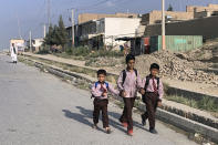 Afghan children walk along a road during the first day of their school's reopening in Kabul, Afghanistan, Saturday, Aug. 22, 2020. Public and private schools in the country were reopened since the beginning of this year due to the coronavirus pandemic. (AP Photo/Rahmat Gul)