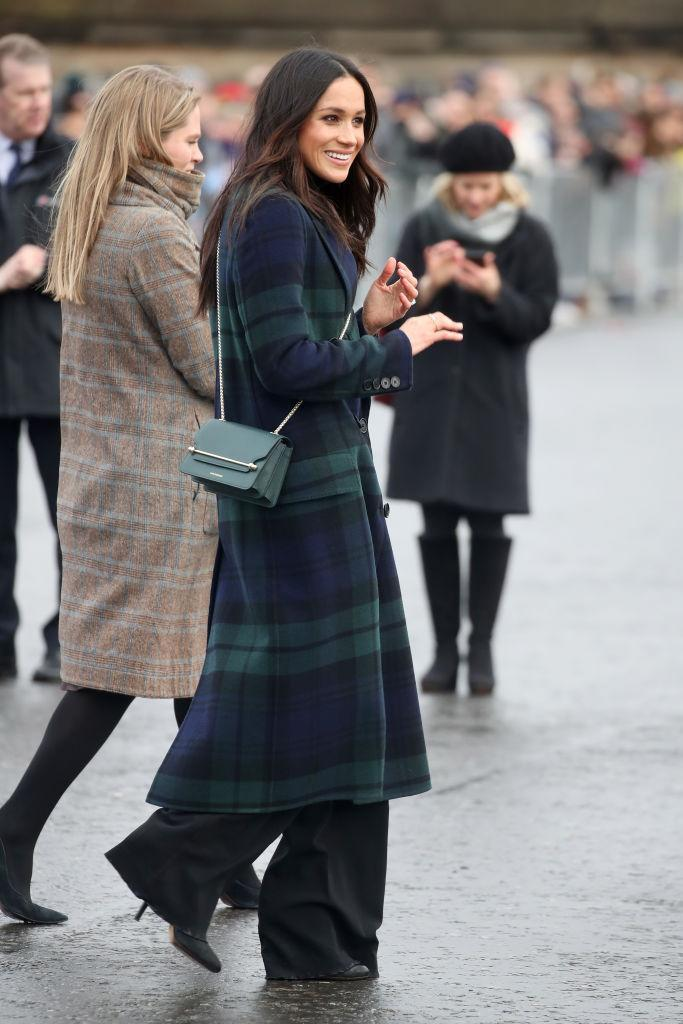 """<p>Prince Harry and Meghan Markle marked their fourth joint royal engagement with a trip to Edinburgh on 13th February. For the occasion, the royal-to-be donned a tartan coat by <a rel=""""nofollow noopener"""" href=""""https://www.net-a-porter.com/gb/en/product/992863?cm_mmc=LinkshareUK-_-gcdL/ATRVoE-_-Custom-_-LinkBuilder&siteID=gcdL_ATRVoE-gH1pIsSzp5E_Cqbl2TE_dQ&Lyst=Lyst"""" target=""""_blank"""" data-ylk=""""slk:Burberry"""" class=""""link rapid-noclick-resp"""">Burberry</a> and accessorised the look with yet another sell-out <a rel=""""nofollow noopener"""" href=""""http://www.lanecrawford.com/product/strathberry/-east-west-mini-leather-flap-suede-crossbody-bag/_/ABR143/product.lc?countryCode=US&utm_source=Affiliates&utm_medium=Affiliates&utm_campaign=Linkshare_US&_country=US"""" target=""""_blank"""" data-ylk=""""slk:Strathberry"""" class=""""link rapid-noclick-resp"""">Strathberry</a> bag. <em>[Photo: Getty]</em> </p>"""