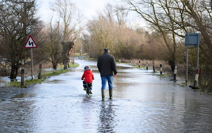 A child cycles along the flooded road by the side of the River Great Ouse after it was closed  - Getty