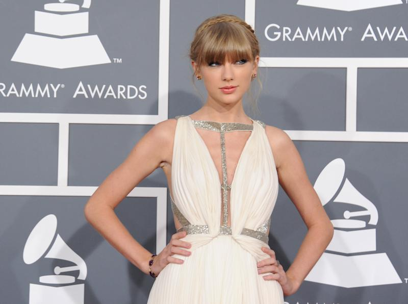 FILE - In this Sunday, Feb. 10, 2013 file photo, Taylor Swift arrives at the 55th annual Grammy Awards in Los Angeles. Swift is a nominee with five nominations at the upcoming 48th annual Academy of Country Music Awards. The show will broadcast live on CBS from the MGM Grand Garden Arena in Las Vegas on Sunday, April, 8, 2013. (Photo by Jordan Strauss/Invision/AP)