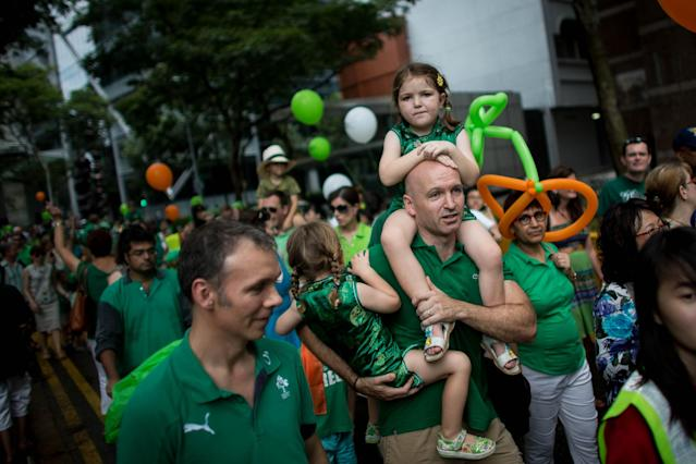 SINGAPORE - MARCH 17: A man carries children down the street during the St Patricks Day Parade at Boat Quay on March 17, 2013 in Singapore. Singapore's Irish community gathered at Boat Quay for a three-day-long St Patrick's Day Street Festival which featured street performances, buskers, and Irish food and drink. (Photo by Chris McGrath/Getty Images)