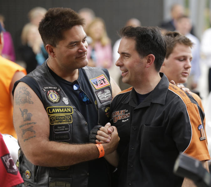 Wisconsin Governor Scott Walker, right, shakes hands with a Harley Davidson rider at the museum Friday, August, 2, 2013 in Milwaukee. The National Governors Association is meeting in Milwaukee. (AP Photo/Jeffrey Phelps)
