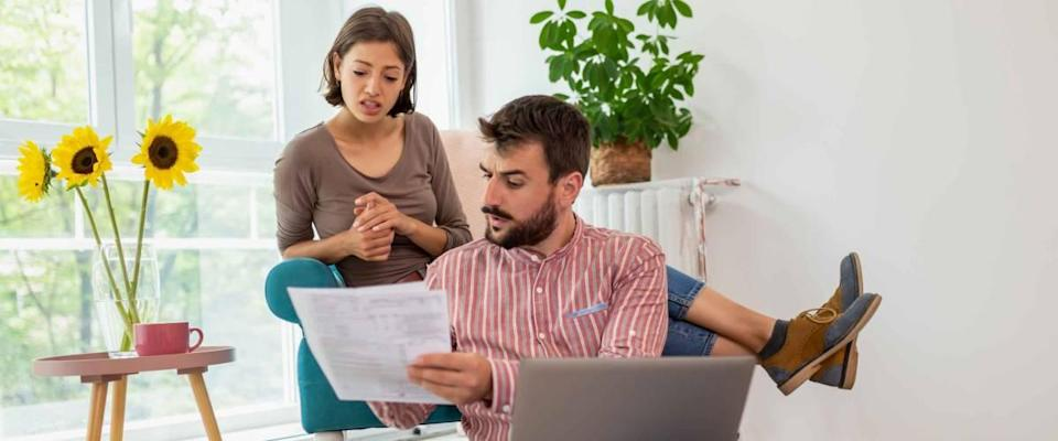 Young couple sitting in living room together, looking at document and looking serious