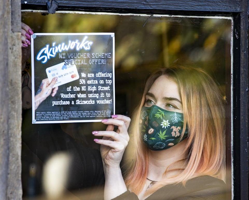 Tattoo apprentice Amy Lawless posts an ad in the window of Belfast City Skinworks, Tattoo and Piercing Studio. The studio is offering 50% extra on top of the Northern Ireland High Street voucher scheme, when using it to purchase a Skinworks voucher (Liam McBurney/PA) (PA Wire)