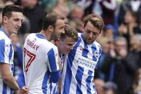 Solly March of Brighton and Hove Albion celebrates with team mates after scoring their second goal