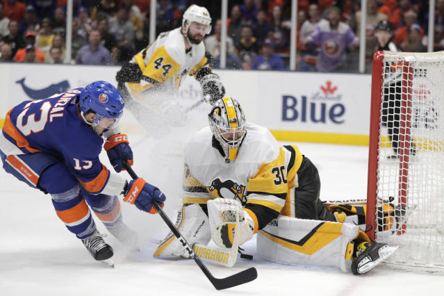 New York Islanders center Mathew Barzal, left, gets a pass by Pittsburgh Penguins goaltender Matt Murray (30) before left wing Anthony Beauvillier scored a goal for the Islanders during the second period of Game 2 of an NHL hockey first-round playoff series Friday, April 12, 2019, in Uniondale, N.Y. (AP Photo/Julio Cortez)