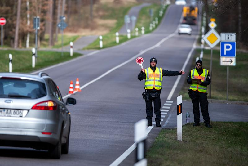 20 March 2020, Mecklenburg-Western Pomerania, Neustrelitz: On the federal road B96, police officers check vehicles that are not registered in Mecklenburg-Vorpommern. With the controls to contain Sars-CoV-2, the state government primarily wanted to prevent a further influx of tourists. Photo: Jens Büttner/dpa-Zentralbild/dpa (Photo by Jens Büttner/picture alliance via Getty Images)