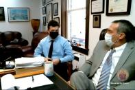 Kyle Rittenhouse sits with lawyer Mark Richards (R) during his remote arraignment by video conference call