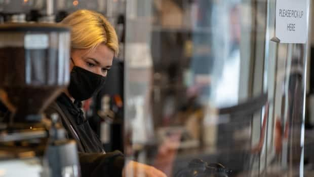 A barista prepares a cup of coffee behind a protective shield at a Bridgehead café in Ottawa on Feb. 22, 2021. (Andrew Lee/CBC - image credit)
