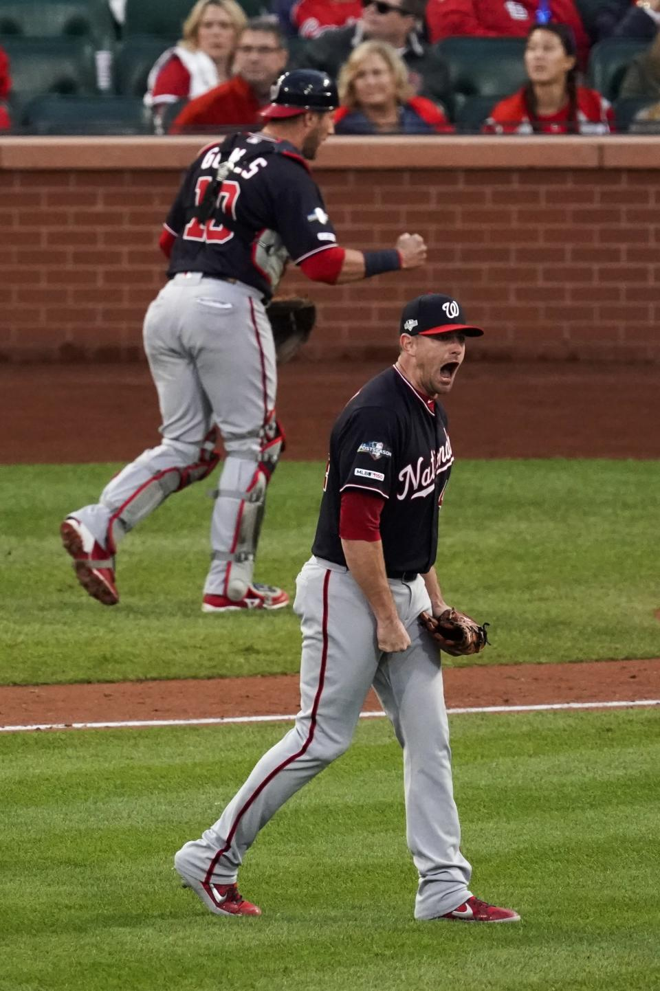 Washington Nationals' Daniel Hudson and Yan Gomes celebrate after Game 2 of the baseball National League Championship Series against the St. Louis Cardinals Saturday, Oct. 12, 2019, in St. Louis. The Nationals won 3-1 to take a 2-0 lead in the series. (AP Photo/Charlie Riedel)