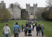 People stroll on The Long Walk towards Windsor Castle in Windsor, England, Saturday, April 10, 2021. Britain's Prince Philip, the irascible and tough-minded husband of Queen Elizabeth II who spent more than seven decades supporting his wife in a role that mostly defined his life, died on Friday. (AP Photo/Frank Augstein)