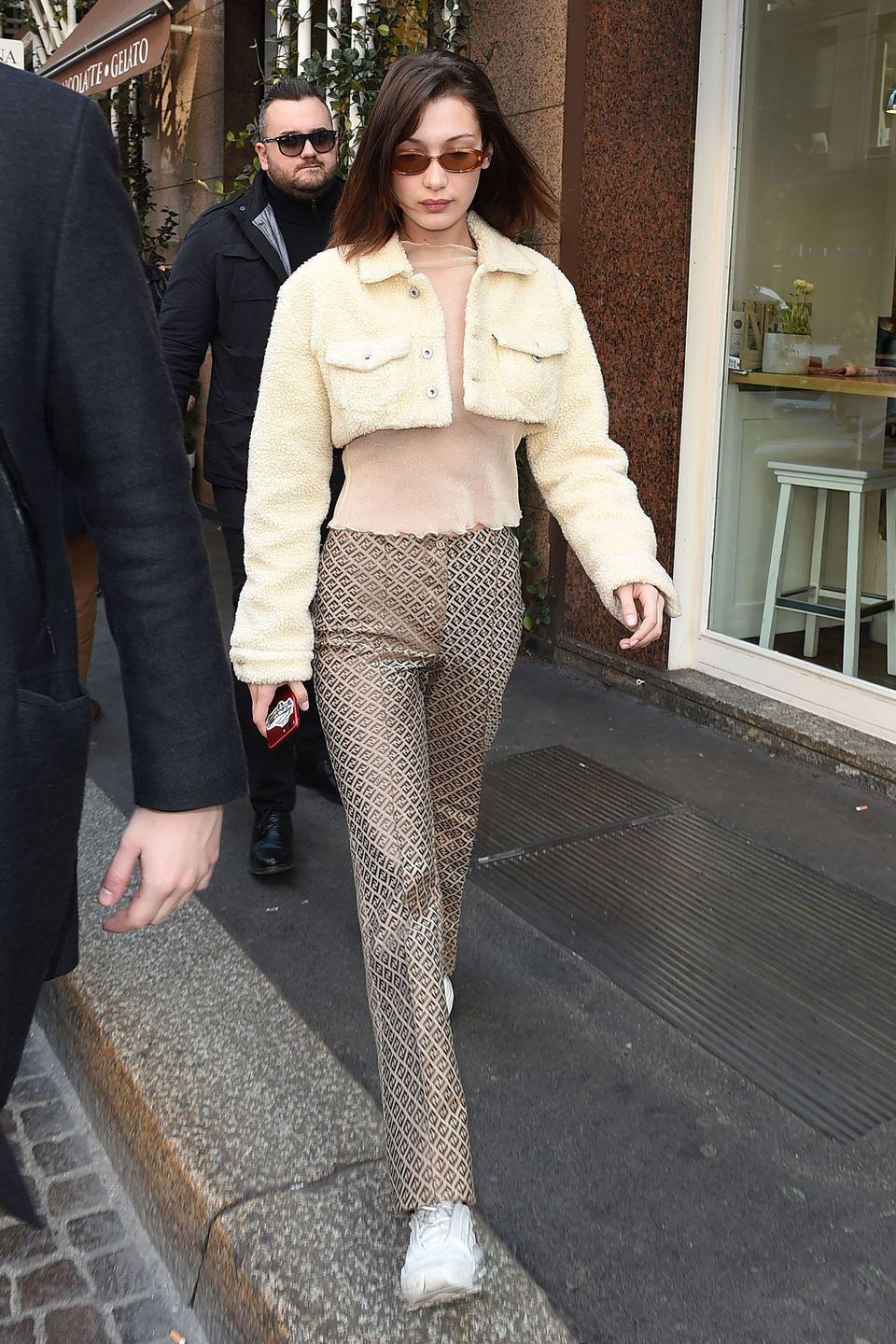"""<p>In Fendi logo-printed pants, a sheer t-shirt under a cropped shearling jacket from the Levi's Made & Crafted x Off-White collection, styled with chunky white sneakers and <a href=""""https://www.shopbop.com/specs/br/v=1/37342.htm?all"""" rel=""""nofollow noopener"""" target=""""_blank"""" data-ylk=""""slk:Le Specs"""" class=""""link rapid-noclick-resp"""">Le Specs</a> sunglasses while out in Milan.</p>"""