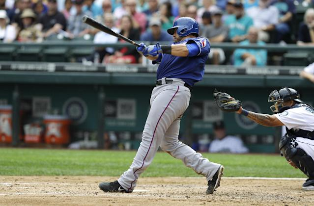 Texas Rangers' Geovany Soto, left, hits a two-run single against the Seattle Mariners in the third inning of a baseball game against the Seattle Mariners, Wednesday, Aug. 28, 2013, in Seattle. (AP Photo/Ted S. Warren)