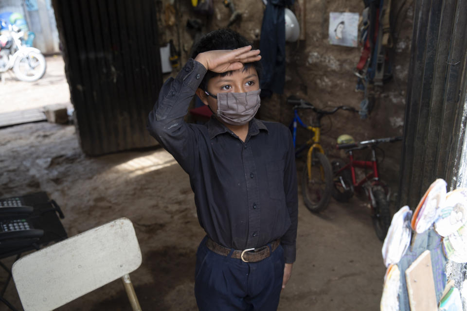 """Standing just inside the doorway of his home in a black button down shirt tucked into navy blue trousers, 11-year-old Oscar Rojas greets his teacher Gerardo Ixcoy, known universally as """"Lalito 10"""", in Santa Cruz del Quiche, Guatemala, Wednesday, July 15, 2020. """"Teacher Lalito only comes for a little while to teach me, but I learn a lot."""" (AP Photo/Moises Castillo)"""