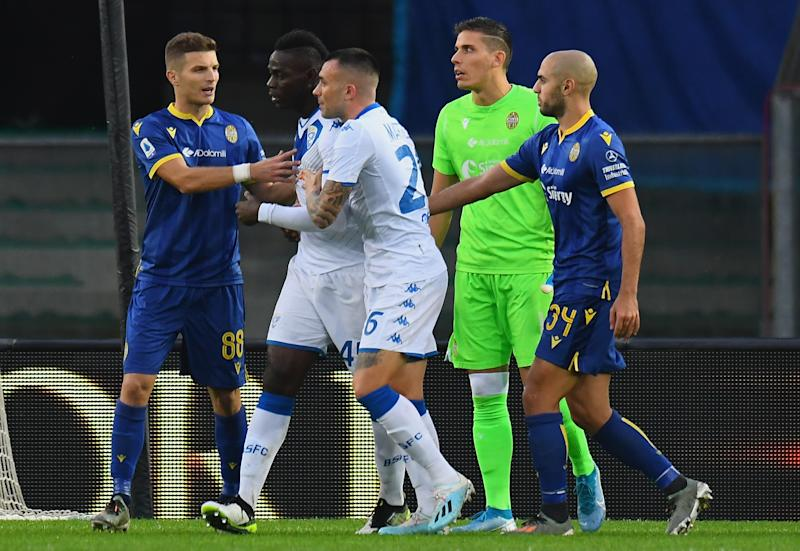 Mario Balotelli attempts to walk off after being targetted by Verona supporters (Getty)