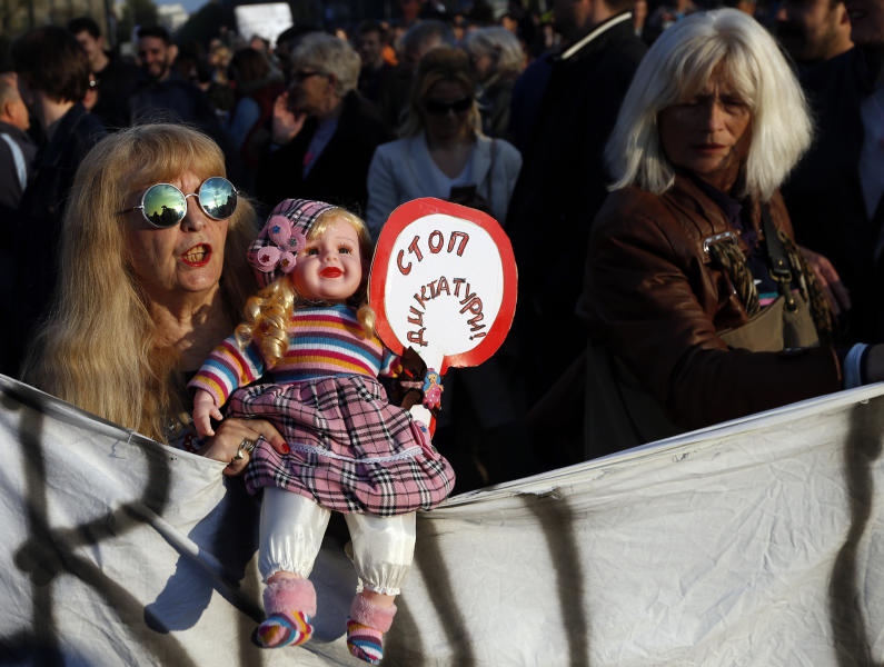 "A woman holds a doll with a banner that reads: ""Stop to dictatorship"", during a protest march in Belgrade, Serbia, Sunday, April 9, 2017. Thousands of people have protested for the seventh consecutive day against the presidential election victory of Serbia's powerful Prime Minister Aleksandar Vucic, amid fresh allegations by the opposition of a rigged vote count. (AP Photo/Darko Vojinovic)"