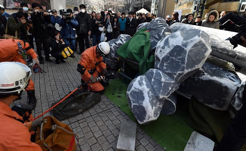 Rescue workers seek 'victims' among the debris during an earthquake drill at the Roppongi Hills shopping complex in Tokyo, in March 2015 (AFP Photo/Toshifumi Kitamura)