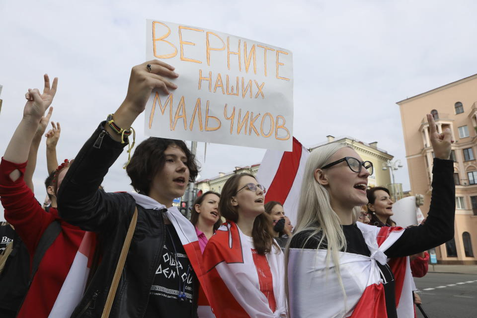 """Women wearing old Belarusian national flags hold a poster reading """"bring our boys back"""" march during an opposition rally to protest the official presidential election results in Minsk, Belarus, Saturday, Sept. 5, 2020. Women's marches and demonstrations have become a regular feature of the four weeks of protest that have shaken Belarus following a disputed election that gave Belarusian President Alexander Lukashenko a sixth term in office. (AP Photo)"""