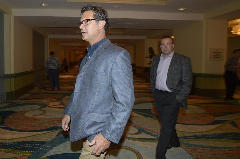 Los Angeles Dodgers manager Don Mattingly, left, heads to a managers reception at baseball's winter meetings in Lake Buena Vista, Fla., Wednesday, Dec. 11, 2013.(AP Photo/Phelan M. Ebenhack)