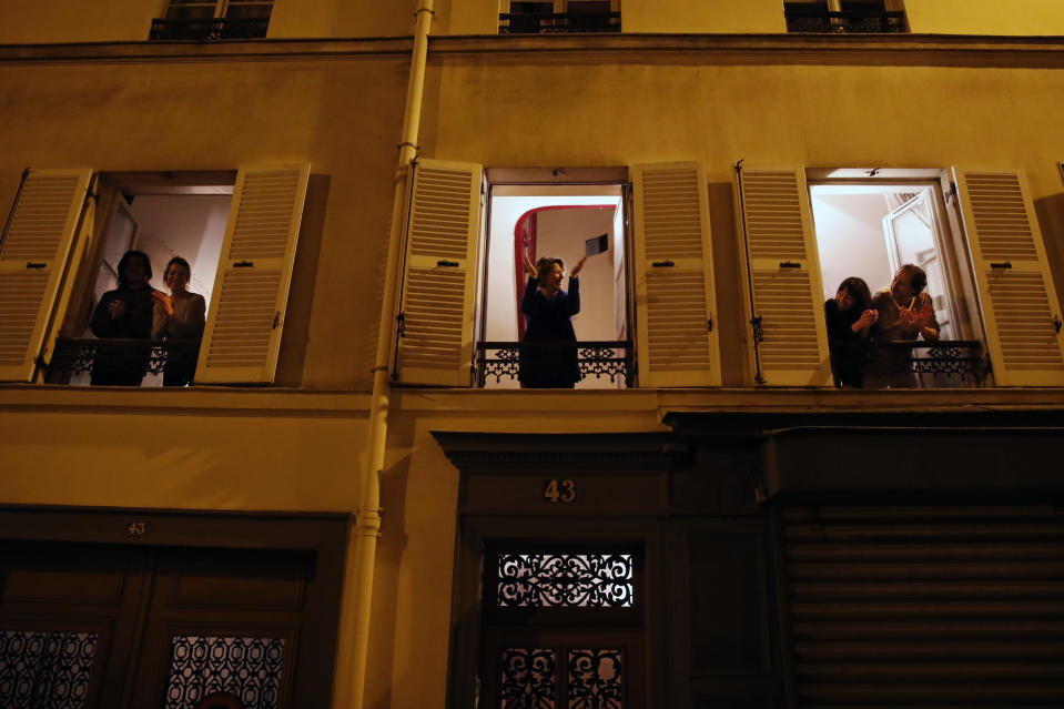 Parisians, in spirit at least, applaud the caregivers and police for their work, as the coronavirus ravaged communities across the country, in Paris, Wednesday, March 18, 2020. In France at 8pm sharp local time French citizens leaned out of windows and dangled from balconies and began applauding and whistling in unison to thank those on the front lines of the pandemic that has already claimed scores of lives. The move was an organized initiative that began circulating on social media. France has been on effective lockdown since midday on Tuesday as French President Emmanuel Macron tightened restrictions on movement to fight the spread of the virus. (AP Photo/Francois Mori)