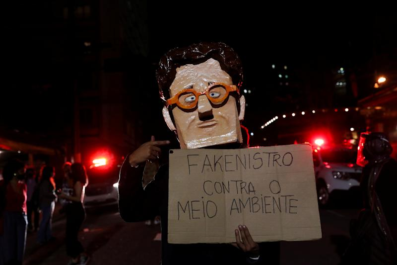 "An activist wears a full head mask depicting Brazil's Environment Minister Ricardo Salles during a protest calling for a ""Global Day of Climate Action"" in Sao Paulo, Brazil, September 25, 2020. The placard reads ""Fake Minister against the environment"". REUTERS/Amanda Perobelli"